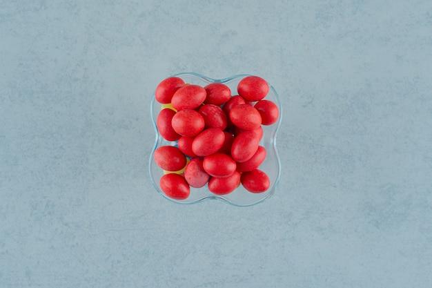 흰색 표면에 달콤한 맛있는 빨간 사탕으로 가득한 유리 접시