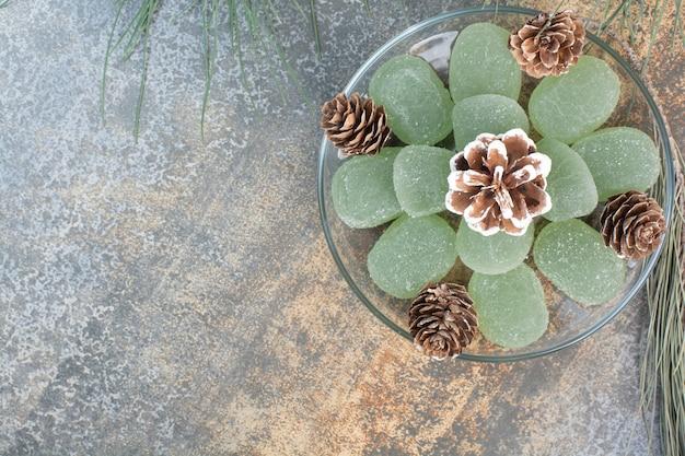 Стеклянная тарелка зеленого мармелада и шишек. фото высокого качества