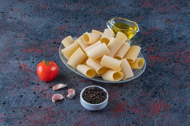 Стеклянная тарелка сырых макарон каннеллони с чесноком и маслом на темной поверхности.