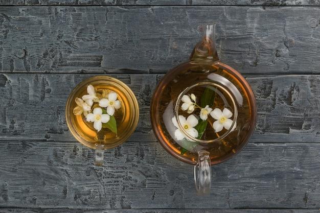 ガラスのティーポットと黒い木製のテーブルの上にライムの花が付いているボウル。健康に良い爽快なドリンク。