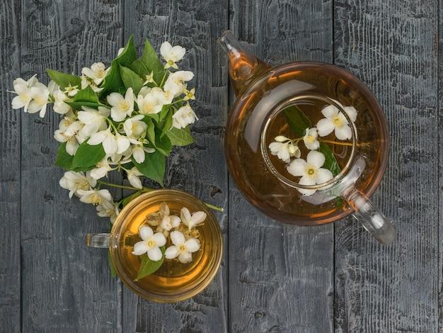 Стеклянный чайник и чашка жасминового чая на деревянной поверхности. бодрящий напиток, полезный для здоровья.