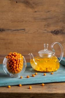 ガラスのティーポットと木製のトレイにシーバックソーンティーが入ったガラスのカップ、健康的なビタミンブライトティー...