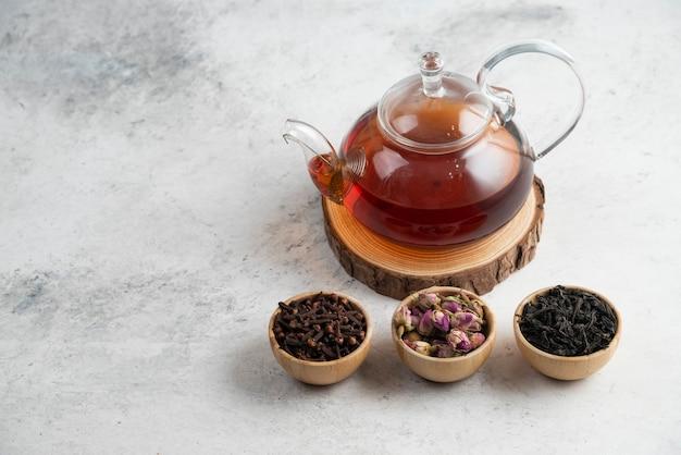 ゆるいお茶の木製のボウルが付いているガラスのティーポット。