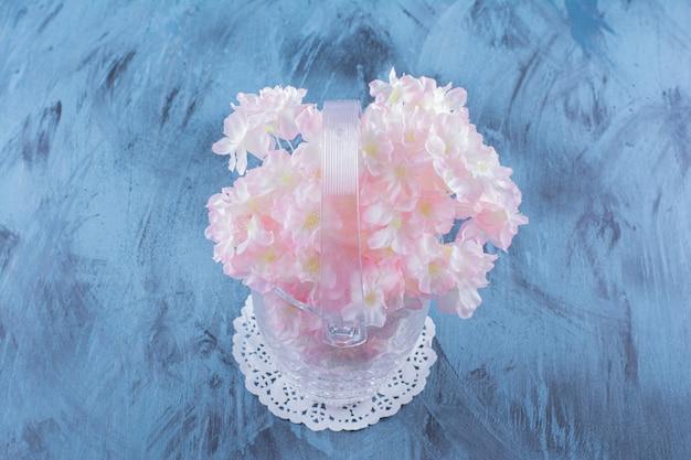파란색에 창백한 꽃의 아름 다운 부케와 유리 꽃병.