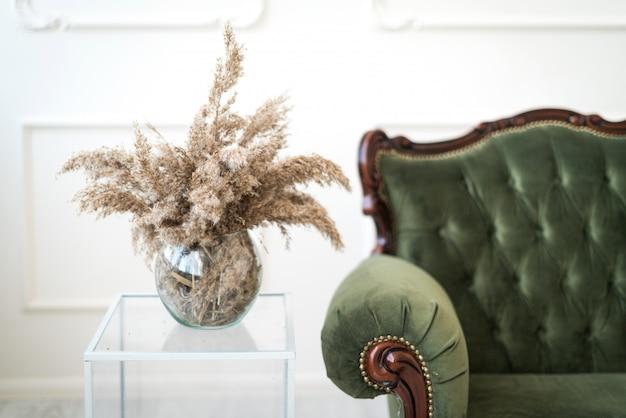 白い壁の背景に緑のビンテージソファの横にある透明なガラスのテーブルの上に、小麦の穂が乾いたガラスの花瓶が立っています。閉じる。ミニマルなインテリアデザイン。
