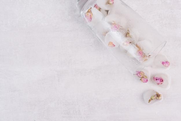 흰색 표면에 얼음과 작은 장미와 유리