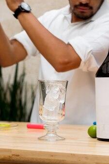 Стакан с кубиками льда на переднем плане на деревянном столе, за спиной молодой человек на заднем плане