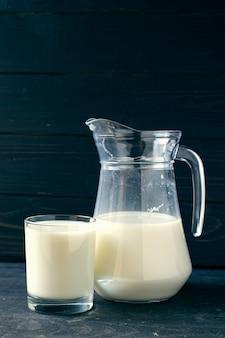 Стакан с молоком и горшок на темном фоне
