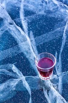 Стакан с красным ликером стоит на льду озера с красивыми трещинами. спирт в стакане и лед присыпанный снегом. вертикальный.