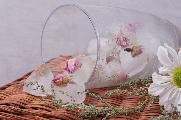 흰색 테이블에 얼음에 작은 장미와 유리.