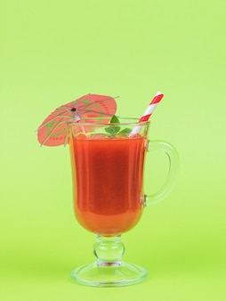トマトジュース、赤いカクテルチューブ、緑の背景に傘が付いたグラス。