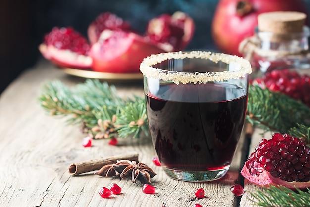 木製のテーブルに新鮮なザクロの果実とモミの木の枝とザクロジュースのグラス。健康的な飲み物のコンセプト。