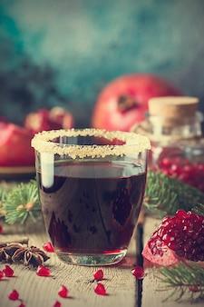 木製のテーブルに新鮮なザクロの果実とモミの木の枝とザクロジュースのグラス