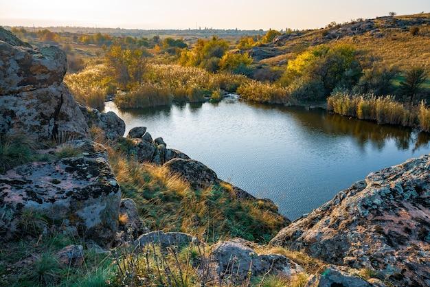 Сверкающая красивая речка среди больших белых камней и зеленой растительности на холмах в украине.