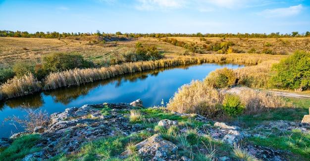 우크라이나의 언덕에 있는 큰 흰색 돌과 녹색 식물 사이에 반짝이는 아름다운 작은 강