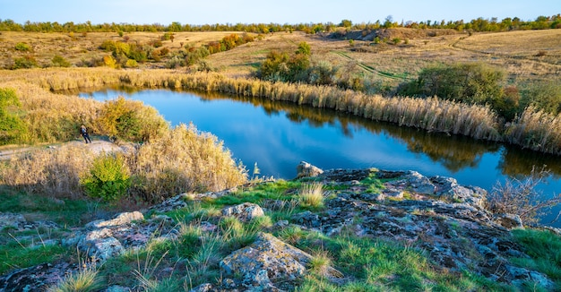 우크라이나의 언덕에 큰 흰 돌과 녹색 식물 사이에 빛나는 아름다운 작은 강
