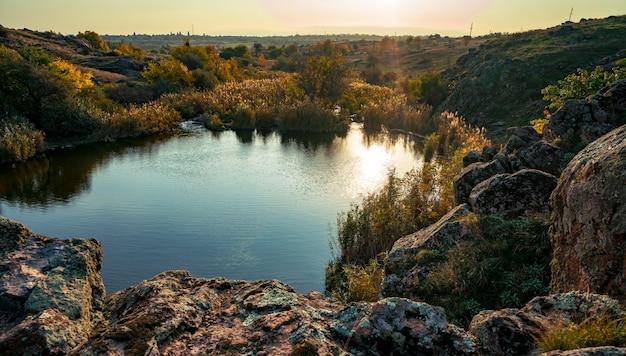 Сверкающая красивая речка среди больших белых камней и зеленой растительности на холмах.