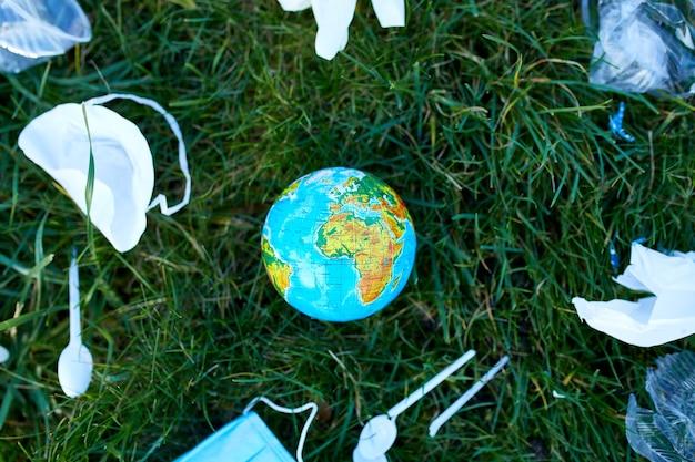 녹색 잔디에 흩어져있는 쓰레기 더미에 지구본