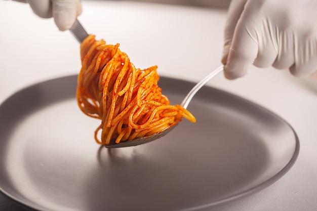 Шеф-повар в перчатке ложкой и пинцетом намазывает пасту в томатном соусе.