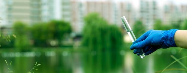 Рука в перчатке набирает воду в пробирку. отбор проб из открытой воды городского водоема. ученый или биолог берет образец воды в пробирке на фоне городского пейзажа