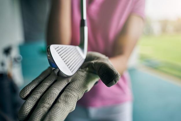 カメラの前でプロゴルファークラブを示す手袋をはめた手