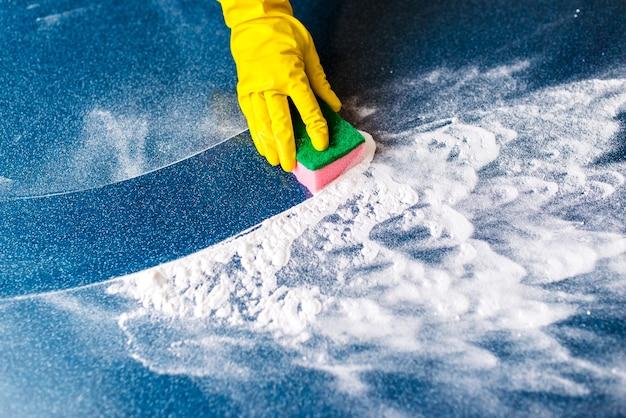 Рука в перчатке вытирает пену и грязь мочалкой. очистка.