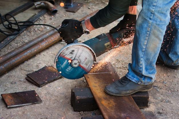 手袋をはめた労働者がアングルグラインダーで金属板を切る火花が砥石から飛ぶ