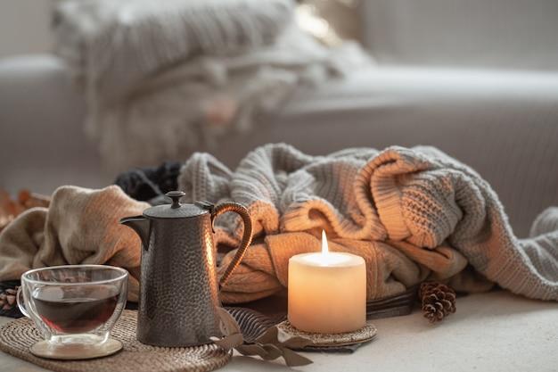 Горящая свеча, чашка чая и чайник на фоне теплых свитеров в комнате.