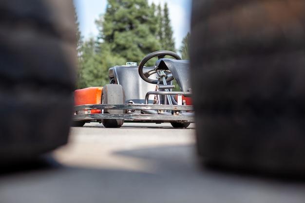 Картинговая машина стоит на трассе и ждет водителя. картинговые автомобили для детей и взрослых.