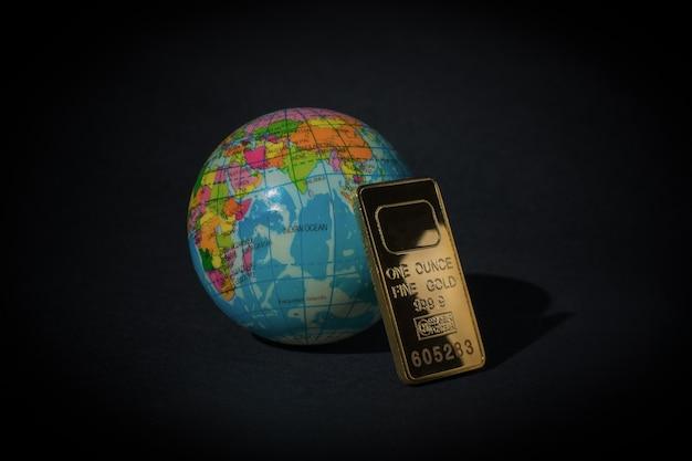 Золотой слиток и глобус на черном фоне. понятие мирового богатства. зависимость от золота.