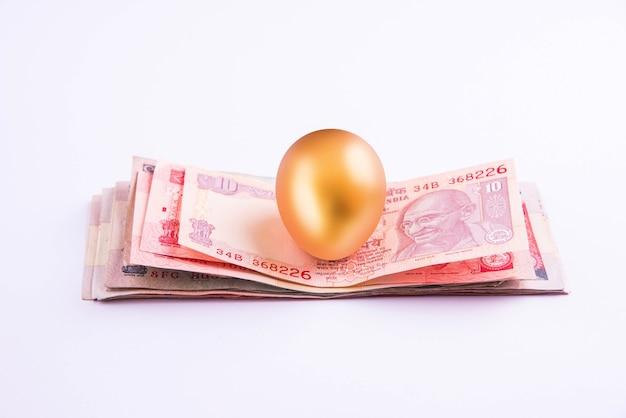Золотое яйцо на стопке индийских денежных знаков