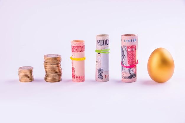 Золотое яйцо, помещенное вертикально в одну линию с рулонами индийских денег или бумажной валюты, перевязанное резинкой, изолированное на белом фоне