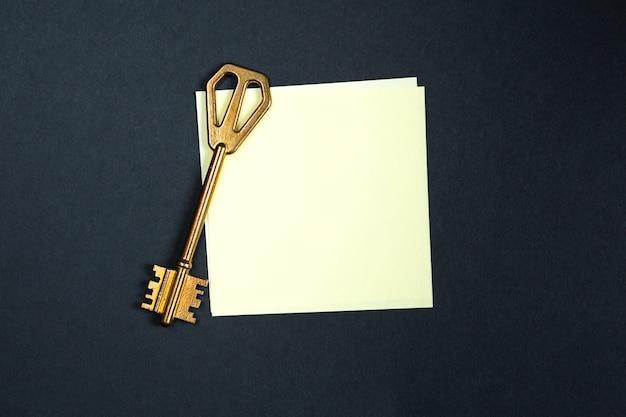 Золотой ключик на листке бумаги для заметок