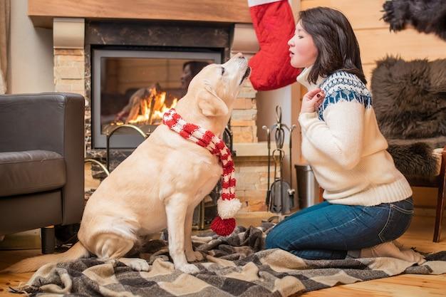 クリスマススカーフのゴールデンレトリバーは、カントリーハウスの暖炉の前の毛布の上に中年のアジア人女性と一緒に横たわっています。