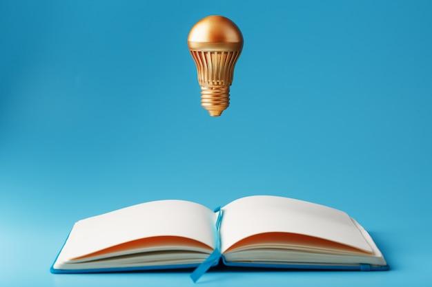 青色の背景に開いているノートブックから浮上で黄金の電球