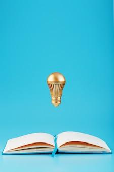 Золотая лампочка в левитации от открытой записной книжки на синем.