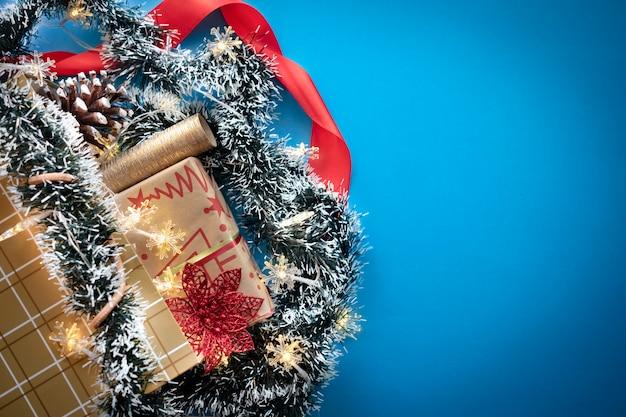 青い背景にクリスマスプレゼントや装飾品が入った金色のショッピングバッグ。コピースペース