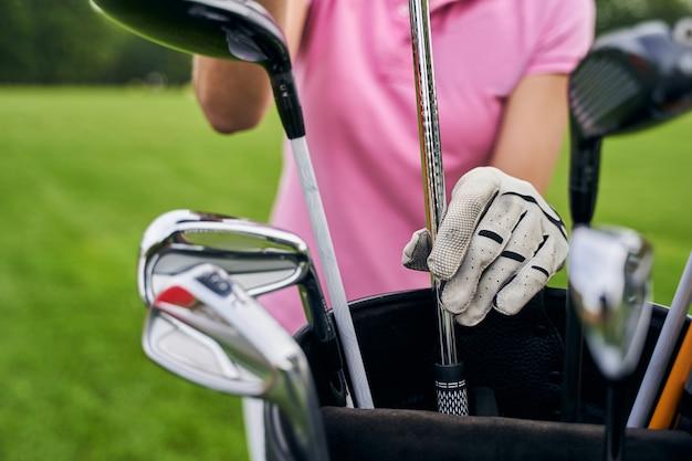 バッグからアイロンを取り出している手袋をはめたゴルファー