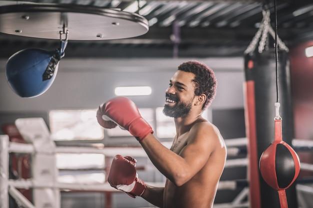 Хороший удар. афро-американский кикбоксер тренируется в тренажерном зале и пинает мешок с песком