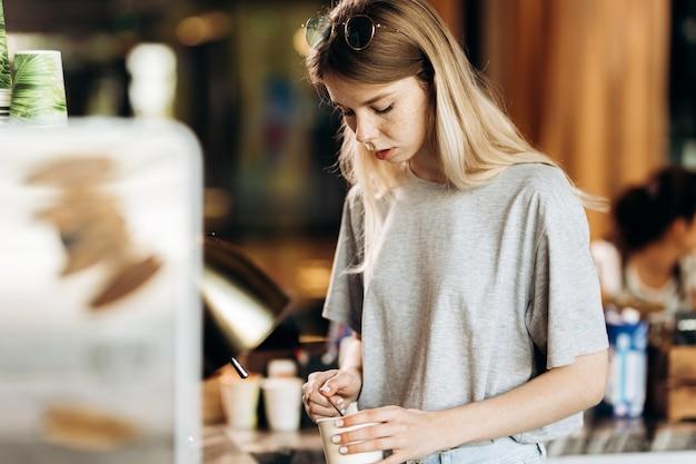 Симпатичная стройная блондинка с длинными волосами, одетая в повседневную одежду, готовит кофе в современной кофейне. показан процесс приготовления кофе. .