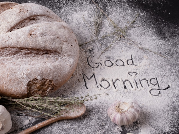 Доброе утро надпись, написанная на муке для выпечки возле домашнего хлеба со специями и чесноком на сером столе