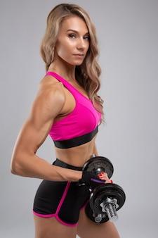 아름다운 운동 몸매를 가진 좋은 섹시한 여자가 아령으로 운동을합니다.