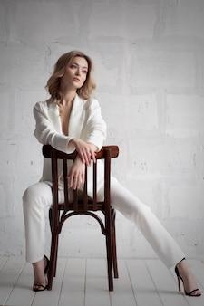 Великолепная блондинка с голубыми глазами и красивой улыбкой в белом расстегнутом костюме и нижнем белье.