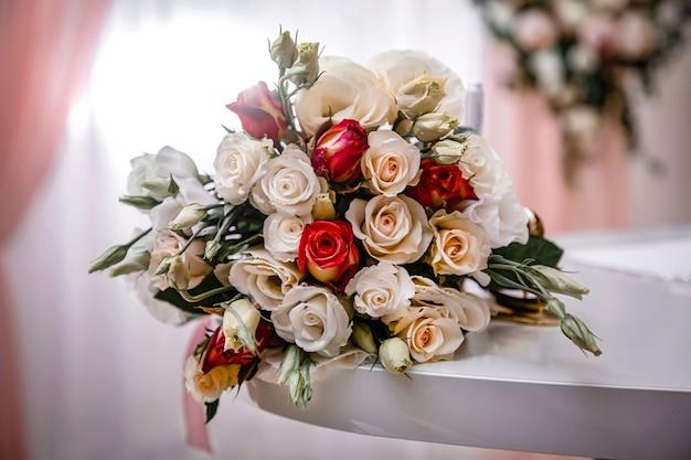 白ピンクと赤のバラの豪華な花束がテーブルの上にあります