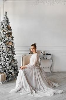세련된 드레스에 화려한 모델 여성이 빈티지 인테리어의 크리스마스 트리 근처에 앉아