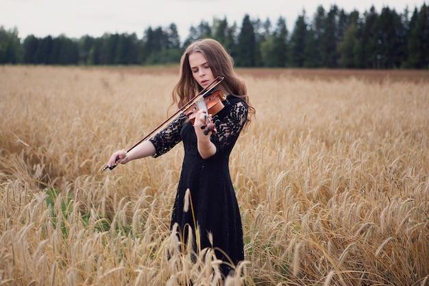 風に吹かれた髪のゴージャスなバイオリニストの女の子が麦畑で曲を演奏します