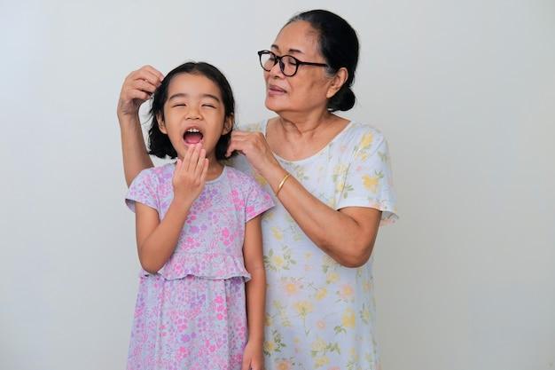 Бабушка поправляет волосы внука, в то время как внук показывает счастливое выражение лица