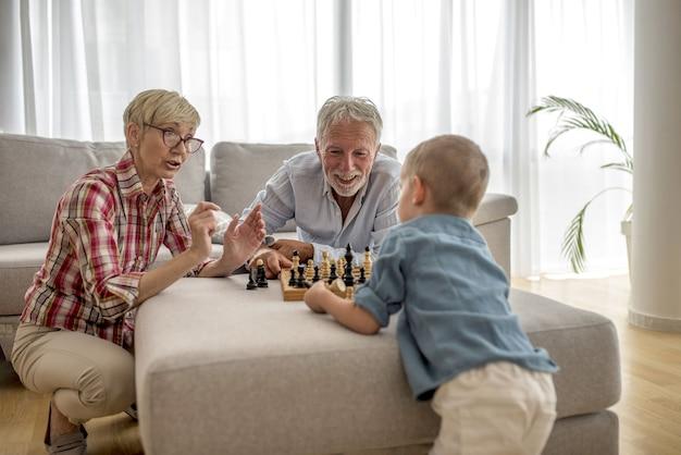 Бабушка и дедушка играют в шахматы с внуком
