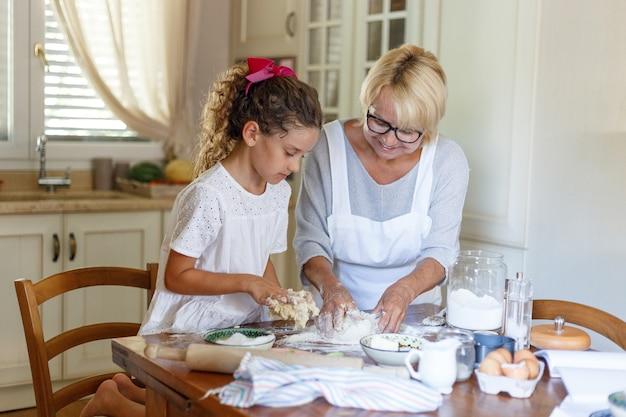 할머니와 조카가 요리를하고 있습니다. 웃는 할머니가 쿠키를 요리하고 있습니다. 가로보기.