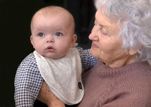 祖母は孫を抱きしめています。赤ちゃんを持つおばあさん。その少年は熱心に見守っていた。